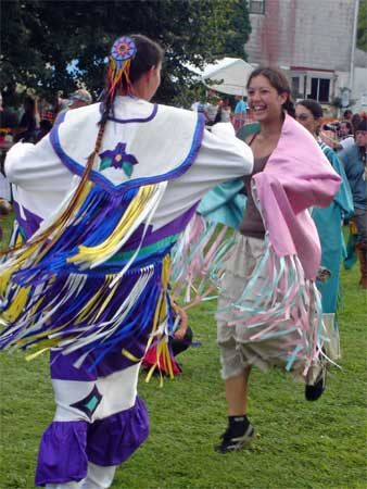 Fancy shawl dancers having showing off their steps and regalia in the circle.